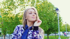 Portrait of a young woman in a city park in the spring. Smiles and dreams Stock Footage