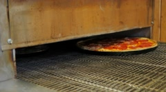 Pizza coming out of  a professional pizza rolling oven - stock footage