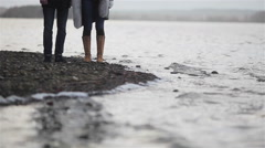 Close up of male and female legs standing at full of stones river bank with wave Stock Footage