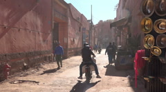 Motorbikes and pedestrians moving though dusty side road Marrakesh Morocco Stock Footage