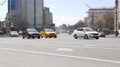 Wide city road, sparse daytime traffic move onward and turn, car slow down Stock Footage