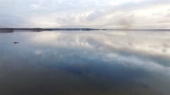 4k aerial - two people stand watching magnificent clouds over calm lake or river Stock Footage