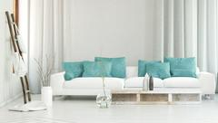 Wide white sofa in front of flowing curtains Piirros