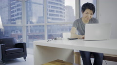 Confident Asian woman in modern condo using laptop online 4K Stock Footage
