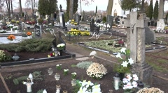 Flowers and candles on grave and people visit dead family members. Tilt up. 4K Stock Footage