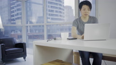 Upset and worried Asian woman in modern condo using laptop online 4K - stock footage