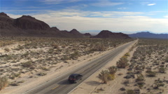 AERIAL: Black SUV car driving along the empty countryside road through desert Stock Footage