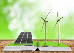 Ecological book with solar panel and wind turbines. - stock photo