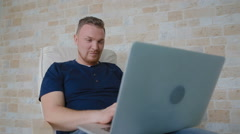 The man easily smiles and corresponds with someone on the laptop Stock Footage