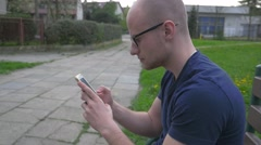 Man sitting on the bench with mobile phone. He is serious. Stock Footage