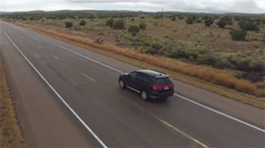 AERIAL: Black SUV car driving on wet empty countryside road in bad rainy weather Stock Footage