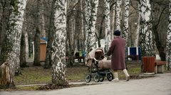 Grandmother with baby carriage walking in the park. Stock Footage