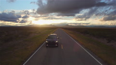 AERIAL: Black SUV car driving along the empty countryside road at golden sunset Arkistovideo