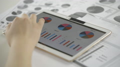 Close-up of hand using tablet to work on business charts and graphs Stock Footage