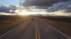 AERIAL: Black SUV car driving along the empty countryside road at golden sunset Stock Footage