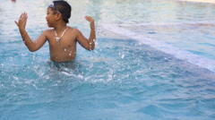 Little boy playing in outdoor swimming pool slowmotion Stock Footage