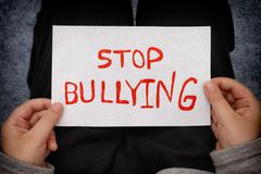 A young boy holds Stop bullying sign - stock photo