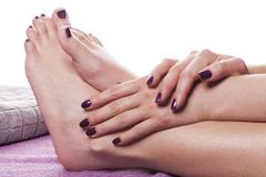 Manicured hands stroke bare feet with nail polish Stock Photos