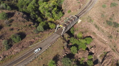 AERIAL: White car driving on empty countryside road over obsolete bridge - stock footage