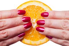 Hand with manicured nails touch an orange on white - stock photo