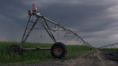 Irrigation in oilseed rape field on cloudy day - stock footage