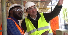 Engineer giving arrangements to a black colleague Stock Footage