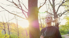 Steadicam slow motion shot: Healthy life - a woman jogging on a spring forest Stock Footage