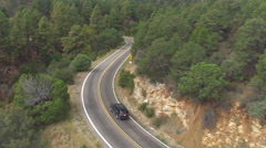 AERIAL: SUV car driving along the winding mountain pass road through the forest Stock Footage