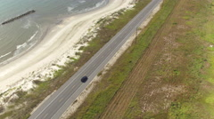 AERIAL: Black SUV car driving on countryside road along the Bay of Mexico - stock footage