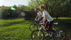 Series of 5 video: Couple riding bicycles on the green meadow at sunset. Stock Footage