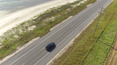 AERIAL: Black SUV car driving on countryside road along the Bay of Mexico Stock Footage