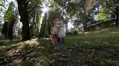 two little sisters having fun on the floral lawn - stock footage