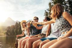 Young people toasting beers on a jetty - stock photo