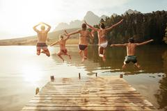 Young friends jumping into lake from a jetty Stock Photos
