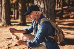 Mature male hiker using digital tablet for navigation - stock photo