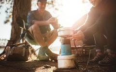 Woman warming hands on stove at campsite Stock Photos