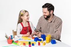 The daughter and father carving out paper applications Stock Photos
