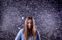 Student against a big blackboard with mathematical symbols - stock photo