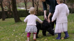 Young mother and two little daughters is playing with dogs on the lawn - stock footage