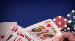 Royal flush in hand and gambling chips on casino blue felt - stock footage