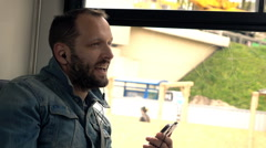 Man sing and listen to music on cellphone during tram ride, super slow motion  Stock Footage
