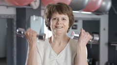 A mature woman lifting dumbbells, senior, fitness Stock Footage
