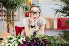 Amusing woman florist making funny face standing in flower shop Stock Photos