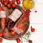 Antipasto catering platter with salami and meat on a wooden background - stock photo