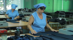 People working on a sewing machine at textile factory - stock footage