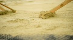 Men raking the sand in the sandpit Stock Footage