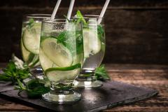 Detox water with a lemon, lime and mint on a wooden table Stock Photos