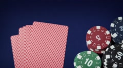 Royal flush in hand and gambling chips on casino blue felt Stock Footage