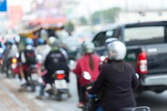 car and motorcycle driving on road with traffic jam in the city, abstract blu - stock photo