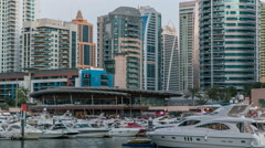 View of Dubai Marina Towers reflected in water of canal in Dubai day to night Stock Footage